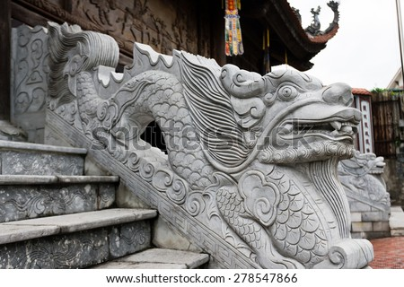 stone dragon statue in Vietnam with face close-up on blue sky background. Leftside view. Symbol of vietnamese mythology and folklore. Religion, culture and art of Asia. - stock photo