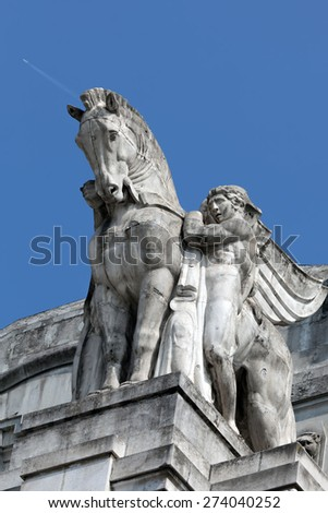 Stone facade of the Milan's main railway station, inaugurated in 1931 is topped with statues of winged horses. - stock photo