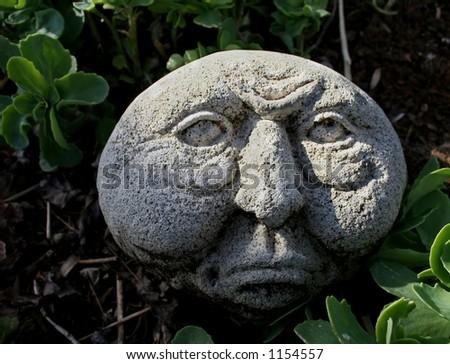 Stone Face in Garden - stock photo