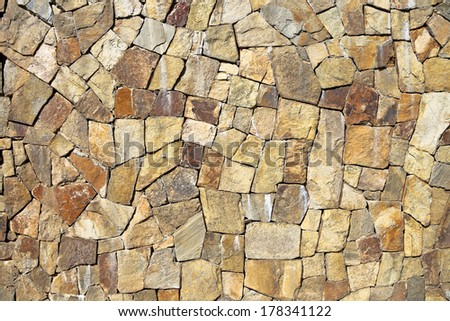 Stone finishing of a wall. Stone texture of warm colours.