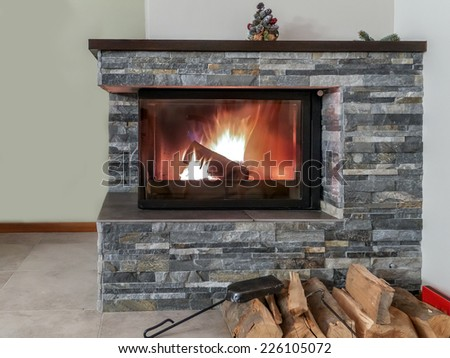 Stone fireplace with lit firewood - stock photo