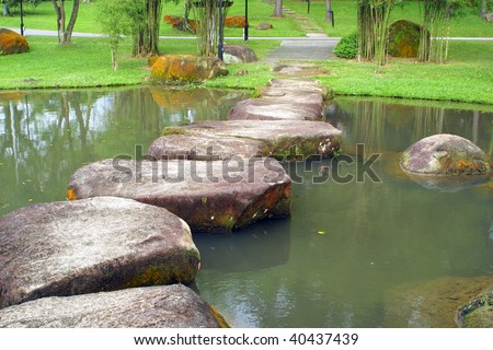 Stone footpath and small lake in the Chinese Garden, Singapore - stock photo