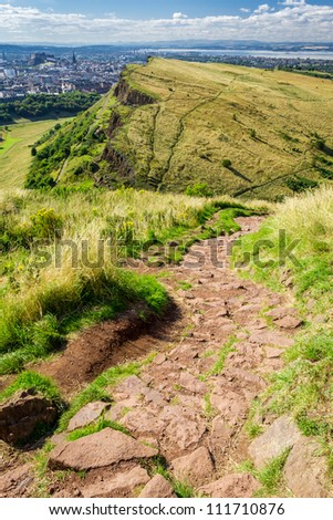Stone footpath in the mountains leading to majestic hill - stock photo