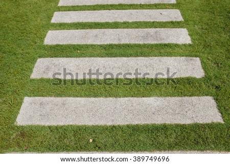 Stone footpath pavement on green grass - stock photo