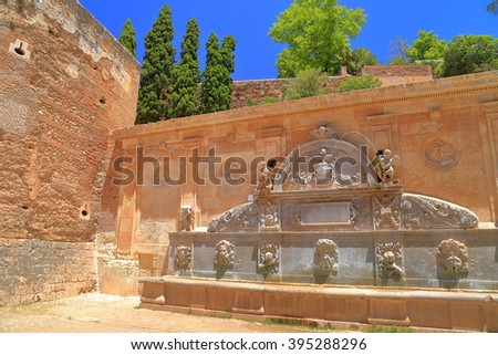 Stone fountain of Charles V surrounded by the medieval walls of Alhambra in Granada, Andalusia, Spain - stock photo