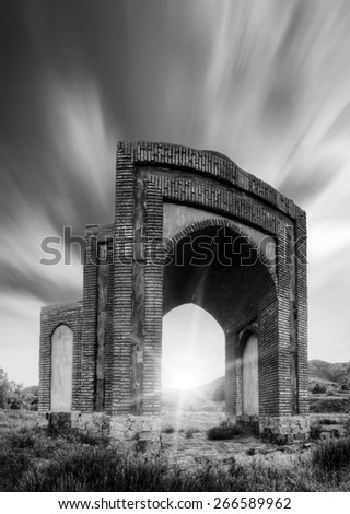 Stone gates in a Crimea mountains with moving dramatic clouds in a sky. Black and white - stock photo