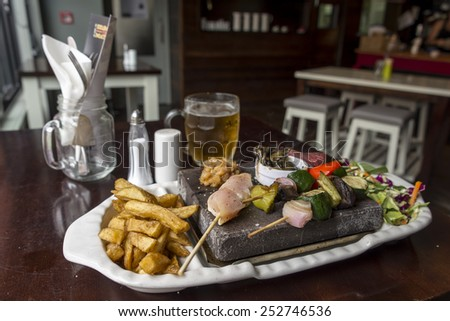 Stone grill steak, chicken and prawn with a mug of beer served in a restuarant