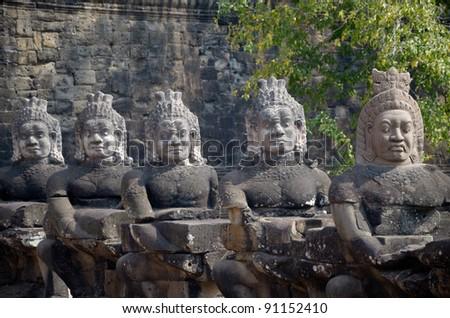 Stone guardians of Angkor Wat gates 1 - stock photo