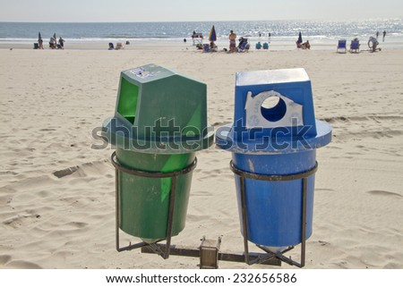 Stone Harbor, New Jersey, USA - September 6, 2014:  Two recycle bins in the foreground on a clean beach with sunbathers by the sea in the distance on September 6, 2014 in Stone Harbor, NJ - stock photo