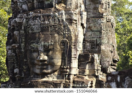 Stone heads which form part of the Bayon Temple in Angkor Thom, near Siem Reap, Cambodia. - stock photo