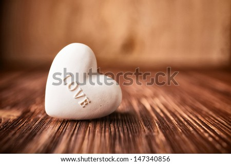Stone heart on a wooden background. - stock photo