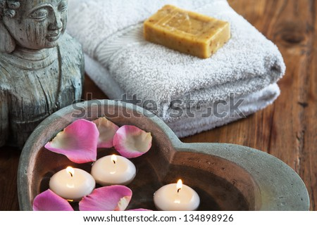 stone heart with water rose petals and floating candles and buddha head and towels with soap in the background
