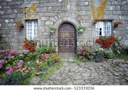 Stone house and flowers garden in Locronan village, Brittany, France