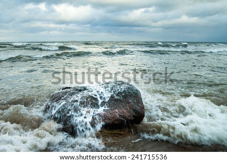 Stone in stormy waves at Baltic sea coast.