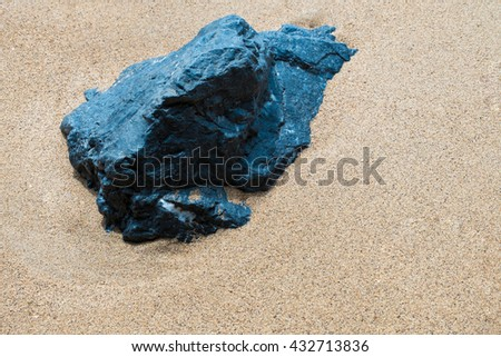 Stone in the sand on the beach - stock photo