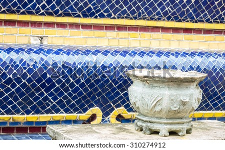 Stone joss stick pot with blue tile wall background - stock photo