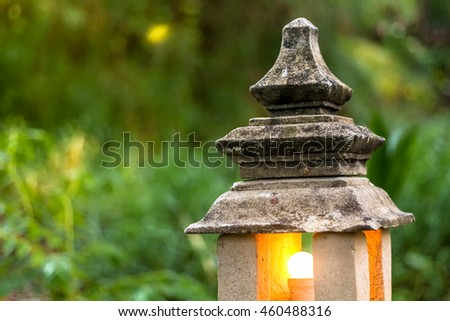 stone lantern lamp with light bulb inside in the green garden forest environment - stock photo