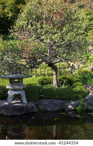 Stone Lantern near pond in japanese garden - stock photo
