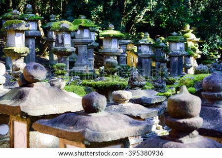 Stone lanterns in Nara, Japan.Foreign texts on the lanterns are for blessing. - stock photo
