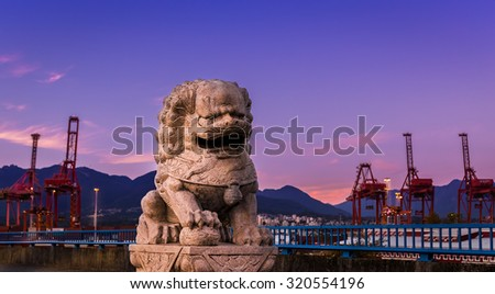 Stone lion statue near the port of Vancouver at sunset.  - stock photo