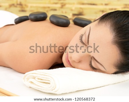 Stone massage for young woman at beauty spa salon. Recreation therapy. - stock photo