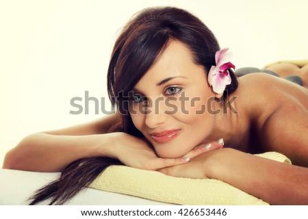 Stone massage, sensual woman getting a hot stone massage at spa salon. Instagram filter.  - stock photo