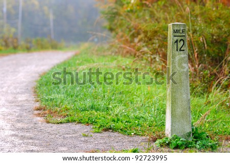Stone mile marker on a hiking/jogging trail - stock photo
