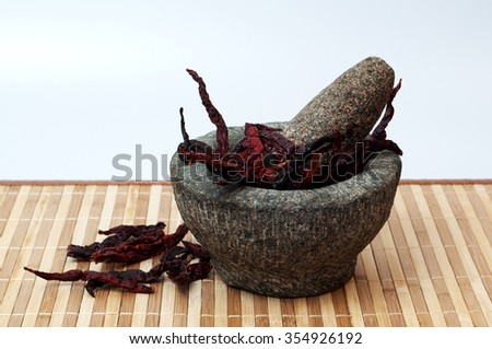 stone mortar and pestle with dry chilies - stock photo