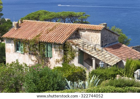 Stone old Mediterranean house with green shutters in the windows, red tiled roof, vine creepers climbing the walls on the edge above the sea - stock photo
