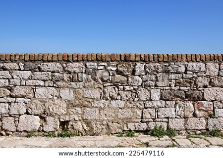 stone old wall with sky in the background - stock photo