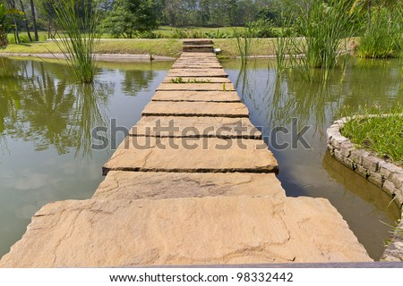 stone path across river to green garden - stock photo