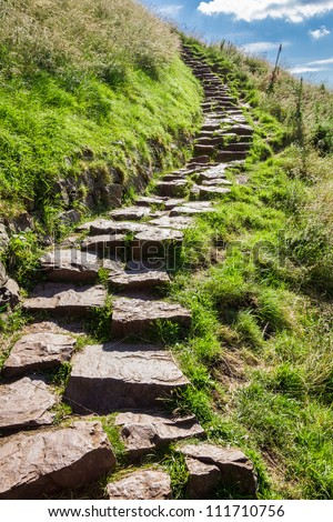Stone path in the mountains leading to the peak - stock photo