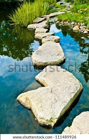Stone path in water garden - stock photo