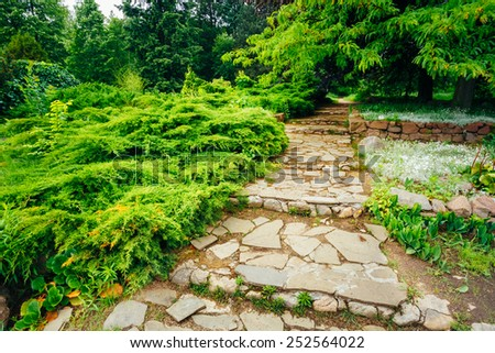 Stone Pathway Walkway Lane Path With Green Trees And Bushes In Garden. Beautiful Alley In Park - stock photo