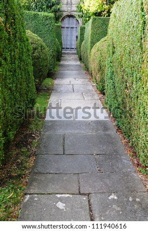 Stone Paved Garden Path with Topiary Sculpting - stock photo