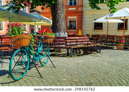 Stone paved old street with cafe bar and old bicycle in Sighisoara fortress,Transylvania,Romania,Europe - stock photo