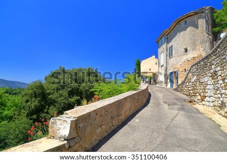 Stone paved road leading to historical buildings in the old town of Menerbes, Provence-Alpes-Cote d'Azur, France