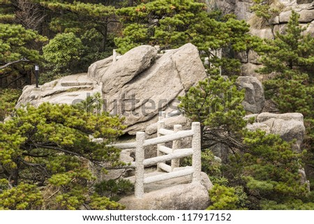 Stone platform in Yellow Mountain park with trees and rocks in background - stock photo