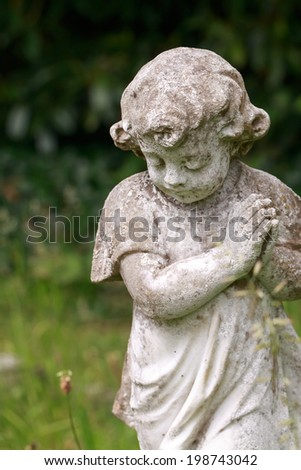 Stone praying child in colour (vertical) - stock photo