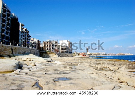 Stone seaside with hotels along on a sunny day in malta - stock photo