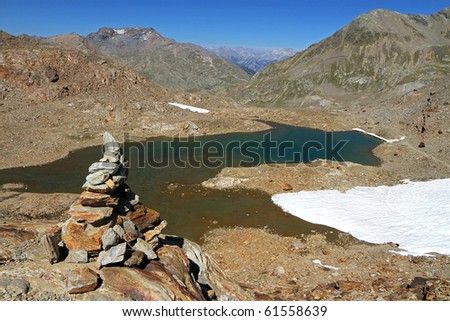 Stone sign along the Valle Umbrina track at 3140 meters on the sea-level. Brixia province, Lombardy region, Italy. Umbrina lake as background - stock photo