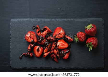 Stone slate plate with strawberry covered with chocolate, above view - stock photo