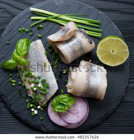 Stone slate tray with herring fillet rolls, onion, lime and basil, top view