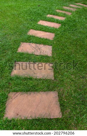 Stone sorted into walkway on the green grass - stock photo