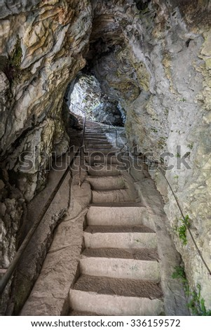 Stone Staircase in a Corridor in the Cave. Passage through the Rock. - stock photo