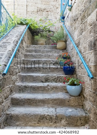 Stone stairs with flowers in front of house entrance. Detail of the facade of home in Jaffa, Israel. - stock photo