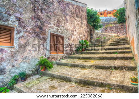 stone stairway in an old narrow street with plants and ruined brick walls. iso 100, heavy processing for hdr tone mapping effect. - stock photo