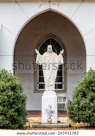 Stone statue of Jesus in the courtyard of a church - stock photo