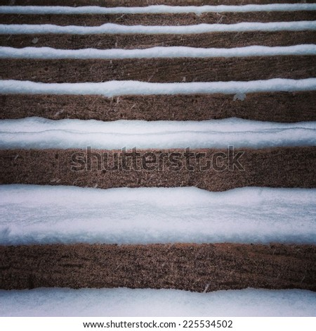 Stone steps covered in a layer of snow. - stock photo