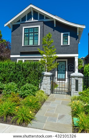 Stone tile paved pathway leading to residential house entrance through metal grid gate - stock photo
